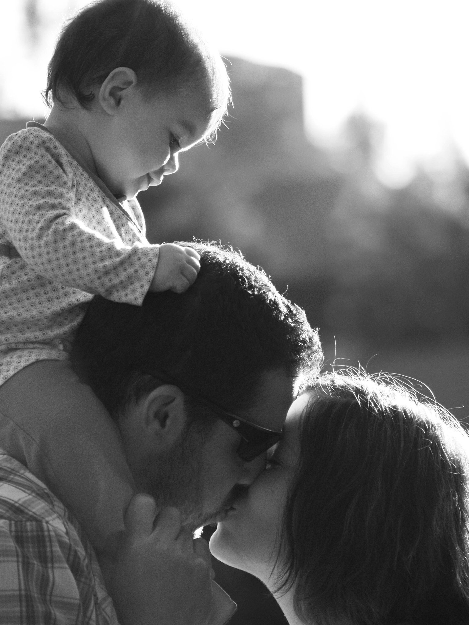 Family portrait of a mother & father kissing, baby on father's shoulders